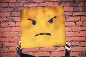 Person holds up stencil of a frustrated expression on a cartoon face.